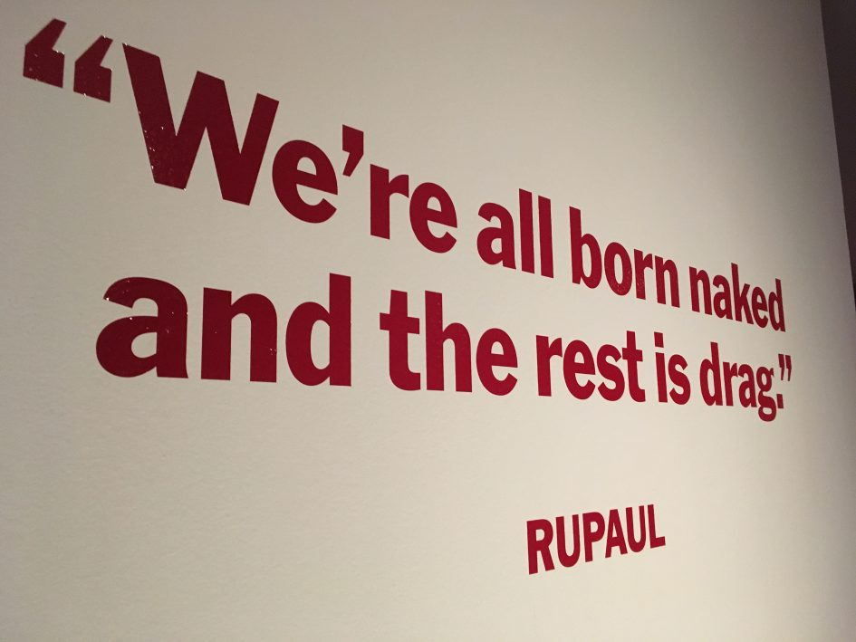 "Roter Schriftzug an einer Wand. ""We're al born naked an the rest is drag"" by RuPaul"